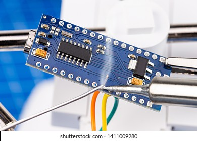 Soldering pins and wires with iron tool of a blue micro controller chip board circuit. Electroncs service technology and macro background.
