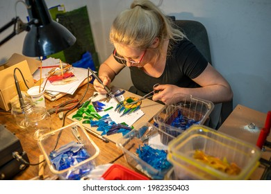 soldering the stained glass window, woman is making a stained glass, stained glass crafting, soldering the stained glass window
