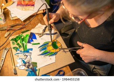 soldering the stained glass window, woman is making a stained glass, piece of glass is lined in foil along the edges, soldering the stained glass window