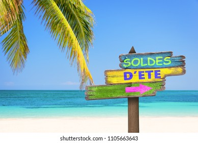 Soldes d'ete (meaning 'summer sale' in French) written on pastel colored wooden direction signs, beach and palm tree background