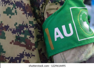 A soldier from the African Union Mission in Somalia (AMISOM), wears a green armband over his camouflage uniform reading AU (African Union), and with the AU flag.