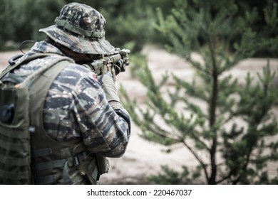 Soldier aiming with rifle - rear view