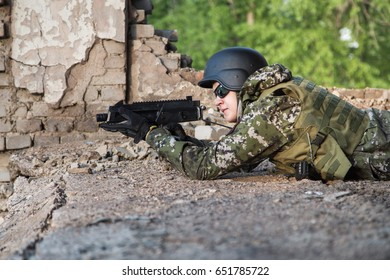 The soldier aims from the combat position. Military actions among the destroyed buildings. Assault and defense