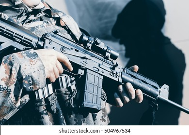 Soldier with assault rifle, officer give orders