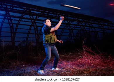 Soldier with axe at night outdoors. Guy military instructor during a military exercise dark night at the military training ground