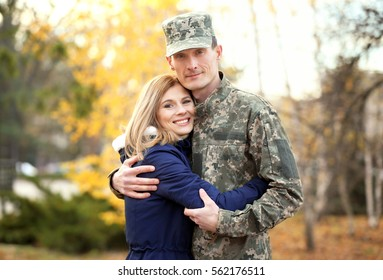 Soldier in camouflage hugging his wife outdoors