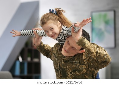 Soldier in camouflage playing with his daughter at home