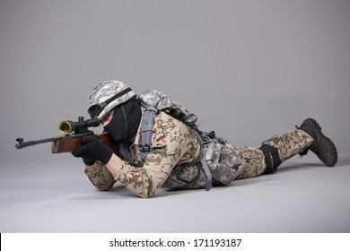 Soldier in camouflage with sniper rifle on the ground