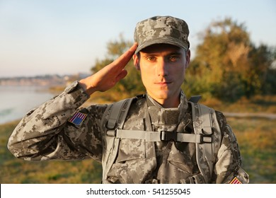 Soldier in camouflage taking salute outdoors