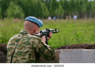 soldier in camouflage uniform with Kalashnikov is shooting