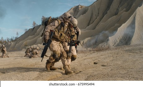 Soldier Carrying Injured One While other Members of Squad Covering Them During Military Operation in the Desert.