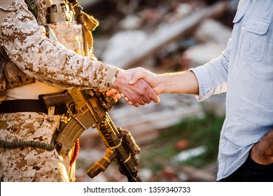 Soldier and civilian shaking hands on outdoor background