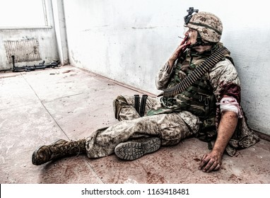 Soldier in combat uniform and ammo belt over chest, sitting on floor and smoking after being shoot in shoulder and put bandage on wounded hand, dropped weapon lying nearby with blood stains around