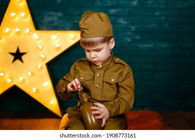 Soldier - the defender of the fatherland. Happy smiling child boy in military uniform. Little patriot. Army thee kid. Portrait of happy young boy in camouflage. Military and rescue operation concept.