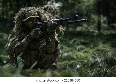 Soldier dressed in ghillie suit in forest
