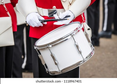 Soldier drummer in red uniform and white gloves playing drum in a march
