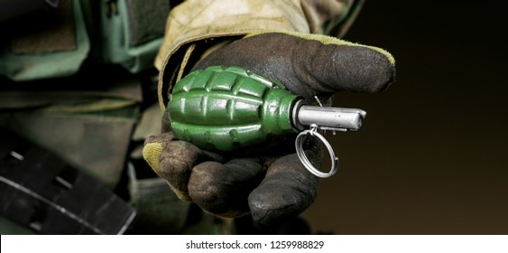 The soldier in full combat ammunition holds a grenade in his hand. Mixed media