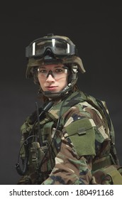 soldier in full gear. Military woman over black background.