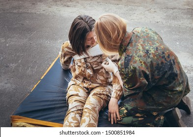 Soldier gives help to the wounded friend. Girl in military uniform. A military girl imposes a bandage on shoulder. Nurse heals friend. Fighting. Aid. Courageous girl soldier. Combat training