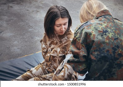 Soldier gives help to the wounded friend. Girl in military uniform. A military girl wearing in hacki helps another warrior. Nurse heals friend. Fighting. Aid. Courageous girl soldier. Combat training