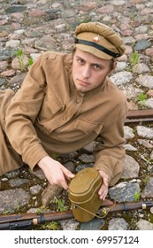 Soldier with gun and boiler in uniform of World War I, resting on the pavement. Costume accord the times of World War I. Photo made at cinema city Cinevilla in Latvia.