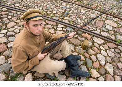 Soldier with gun and boiler in uniform of World War I, sit down and resting on the pavement. Costume accord the times of World War I. Photo made at cinema city Cinevilla in Latvia.
