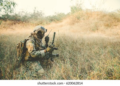 Soldier with gun in had sit in the forest,He's using walkie talkie to call for backup,military in war concept