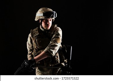 Soldier with gun is on mission on black background. Concept of war.