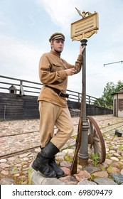 Soldier with a gun in uniform of World War I, smoking at tram stop. Costume accord the times of World War I. Photo made at cinema city Cinevilla in Latvia.