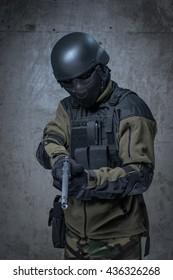 Soldier in helmet and camouflage with big gun in hands