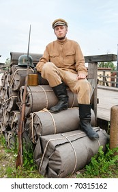 Soldier with helmet and gun sitting on the bundles. Costume accord the times of World War I. Photo made at cinema city Cinevilla in Latvia.