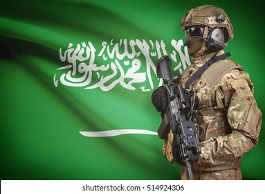 Soldier in helmet holding machine gun with national flag on background - Saudi Arabia