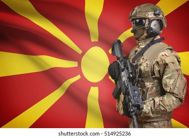 Soldier in helmet holding machine gun with national flag on background - Macedonia