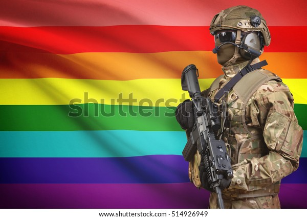 Soldier in helmet holding machine gun with national flag on background - LGBT people