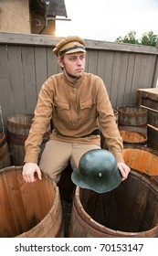 Soldier with a helmet sitting on the butt. Costume accord the times of World War I. Photo made at cinema city Cinevilla in Latvia.