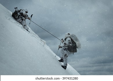 Soldier helping another to climb up the hill. Two military men in the background of a winter landscape