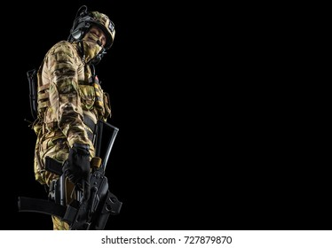 Soldier holding assault rifle. Uniform conforms to special services of the Russian Federation. Shot in studio. Isolated with clipping path on black background