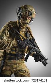 Soldier holding assault rifle. Uniform conforms to special services of the Russian Federation. Shot in studio. Isolated with clipping path on grey background