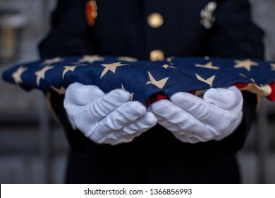 Soldier holding folded American Flag
