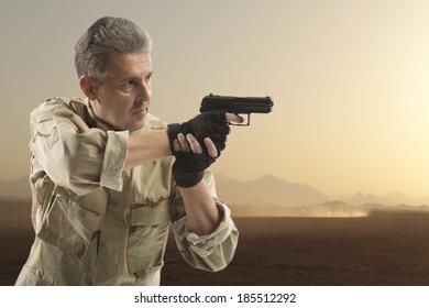 Soldier Holding Gun against an desert background