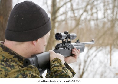 Soldier or hunter is aiming or shooting