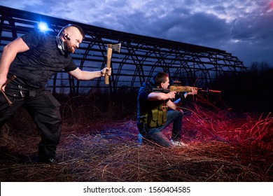 Soldier and instructor at night outdoors. A short man paratrooper and a large brutal male instructor during a military exercise dark night at the military training ground