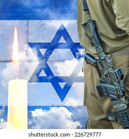 Soldier of Israeli defense forces on Israeli national flag wall and sky background with burning candle