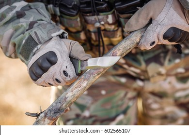 soldier with a knife cut a wooden stick. People and military concept