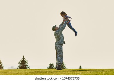 Soldier lifting up little kid. Father in military uniform is playing with daughter in the park.