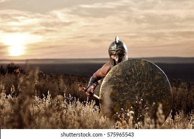 Soldier like spartan in bronze helmet holding  rounded shield.