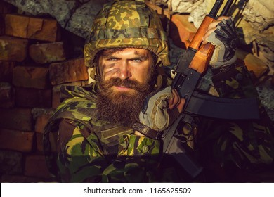 Soldier man with young bearded wicked angry dirty face in military helmet on head and rifle in hands wearing army ammunition sitting in stone brick ruins.