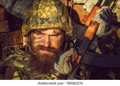 Soldier man with young bearded wicked angry dirty face in military helmet on head and rifle in hands wearing army ammunition sitting in stone brick ruins