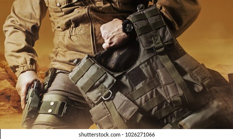Soldier in military outfit with bulletproof vest. Photo of a soldier in military outfit holding a gun and bulletproof vest on orange desert background.