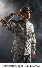 soldier in military uniform and cap giving salute on black with smoke